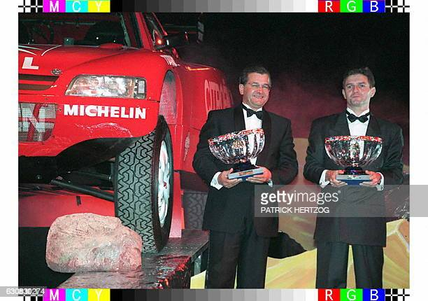 French Pierre Lartigue and his copilot Michel Perin pose with their rally raid world championship trophees 06 December in Monaco during the...
