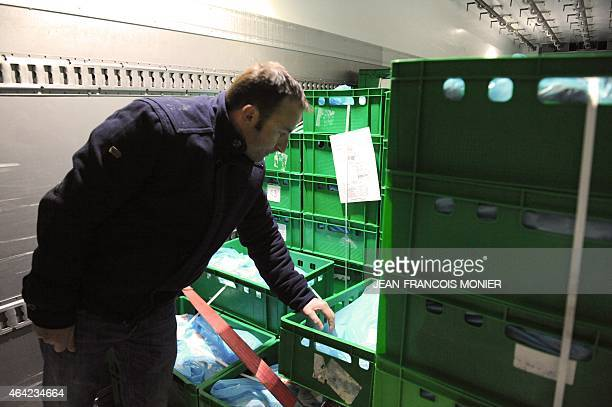 A French pig farmer checks the meat content in a refrigerated truck arriving at the in the 'Rillettes' Luissier Bordeau Chesnel plant in Champagne...