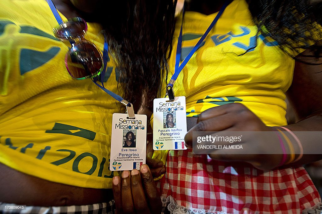 French pilgrims show their identification cards at a party organized by the Brazilian Catholic Church during in Sao Goncalo municipality, 30km from Rio de Janeiro, Brazil on July 17, 2013. The Brazilian Catholic Church confirmed the attendance of over 300 thousand foreign pilgrims for the World Youth Day (WYD) to be held in Rio next July 22 to 28 with the presence of Pope Francis.