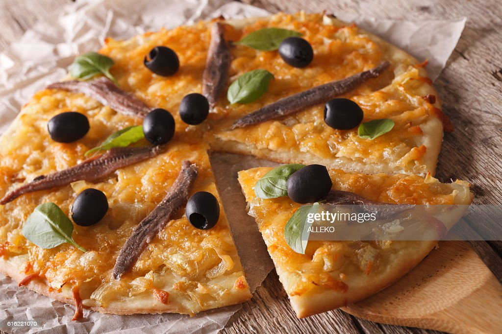 French Pissaladiere with anchovies and onions close-up. horizontal : Stock Photo