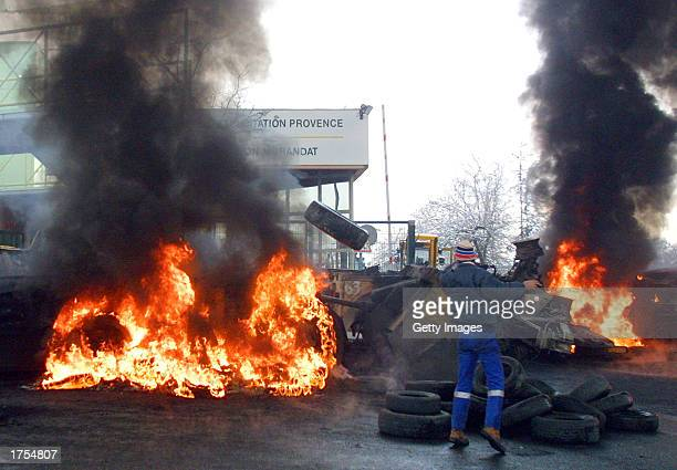 French pit worker throws a tire on a burning barricade as miners block the entrance of the mine shaft in Gardanne France on January 31 2003