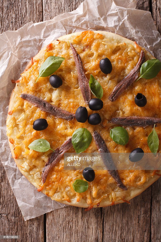 French pizza Pissaladiere close-up on the table. vertical top view : Stock Photo