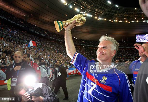 French player Didier Deschamps holding the world cup trophy salutes the crowd after the football exhibition match between France's 1998 World Cup...