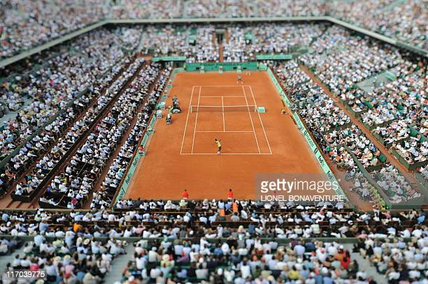 French player Gael Monfils serve a ball to Swiss Federer Roger Federer during a French Open tennis quarter final match on June 3 2009 at Roland...