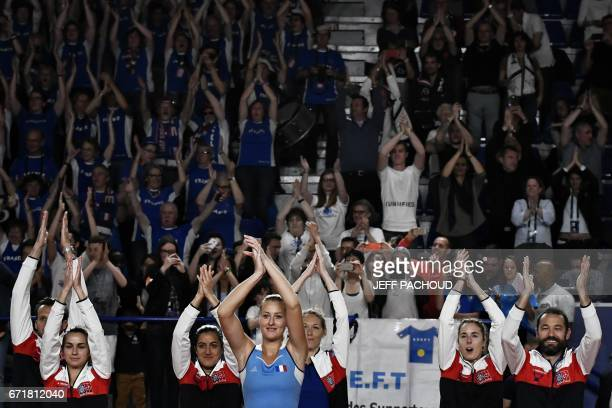 French player Kristina Mladenovic celebrates with France's team after winning her game Spanish player Sara Sorribes Tormo during the Fed Cup tennis...