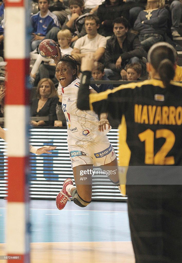 French player Siraba Dembele (L) takes a shoot during the friendly women's handball match France vs Spain, on November 30, 2012 at the Palais des victoires sports hall, in Cannes, southeastern France.