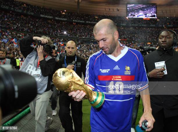 French player Zinedine Zidane holding the world Cup trophee salutes the crowd after the football exhibition match between France's 1998 World Cup...