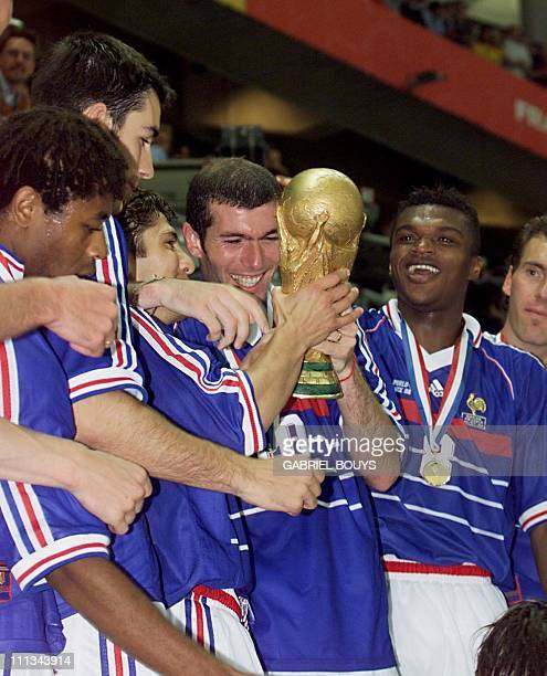French players Bernard Diomede Robert Pires Bixente Lizarazu Zinedine Zidane Marcel Desailly and Laurent Blanc celebrate with the 1998 FIFA Trophy...