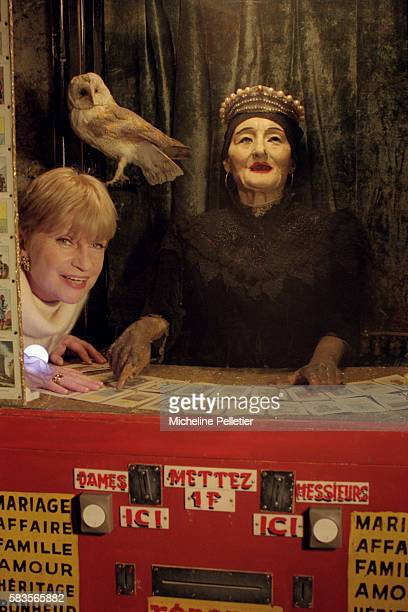 French playwright Francoise Dorin stands next to a fortunetelling machine at the Musee des Arts Forains a museum of fairground art in Paris