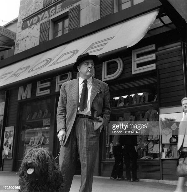 French poet Jacques Prevert and his dog in front of the 'cafe de la Merode' in 1955 in Paris France