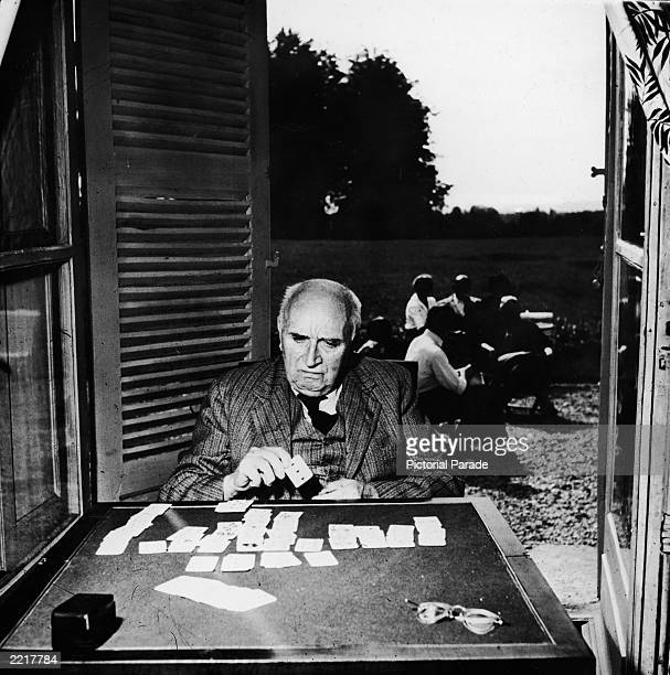 French poet playwright and diplomat Paul Claudel plays a game of solitaire by an open doorway circa 1950