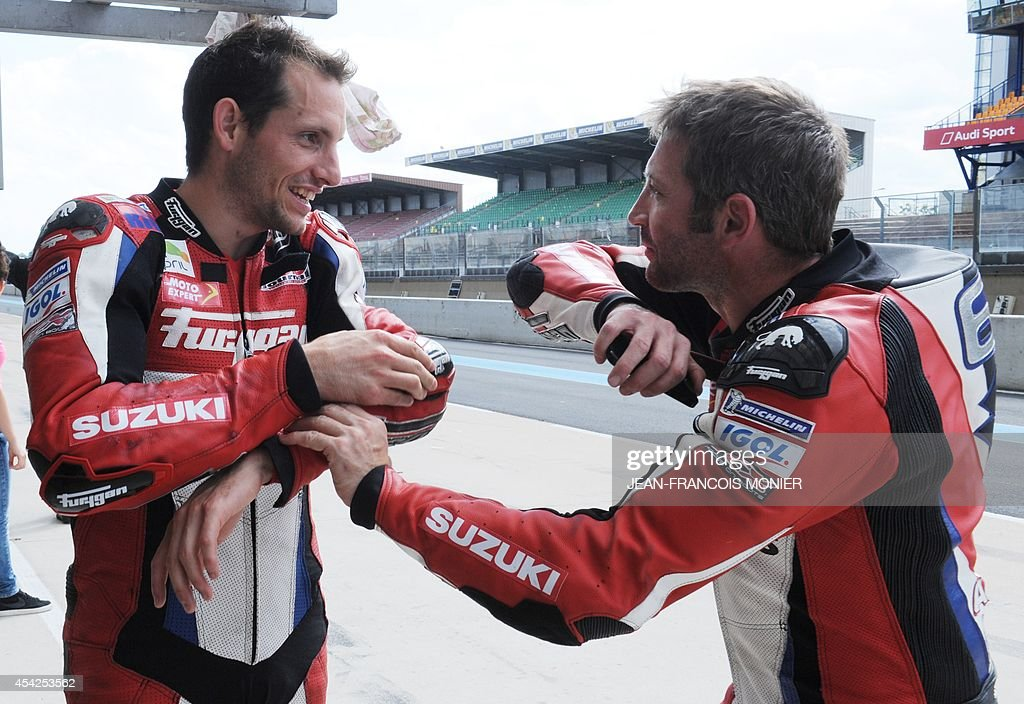 French pole vault world record holder Renaud Lavillenie (L) talks with French rider David Dumain during a training practice session of the Le Mans 24-Hour endurance moto race on August 26, 2014, in Le Mans, western France. Lavillenie will take the start of the race on a Suzuki GSXR motorcycle on September 20, 2014.
