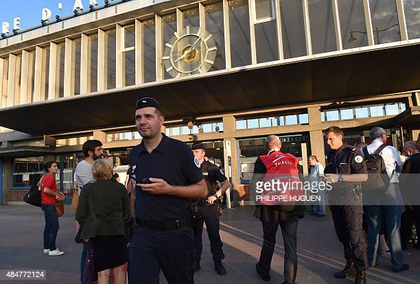French police and train personnel stand outside the main train station in Arras northern France on August 21 2015 A gunman opened fire on a train...