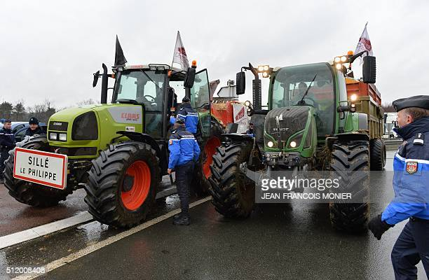 French police attempt to prohibit farmers from blocking the entrance to the highway near Le Mans as they protest against falling prices of dairy and...