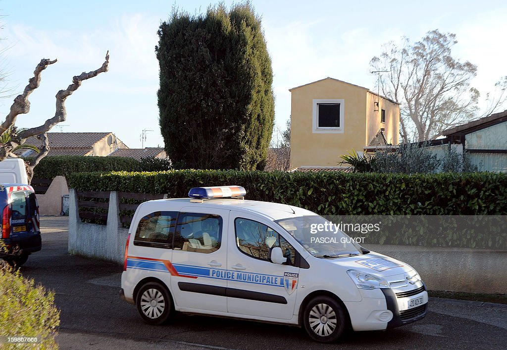 A French police car is parked outsiderk outside a house where five people were found dead on January 22, 2013 in Garons, near Nimes, southern France. The bodies of two adults and three children were found by firemen after a neigbour called for a fire in the afternoon. AFP PHOTO / PASCAL GUYOT