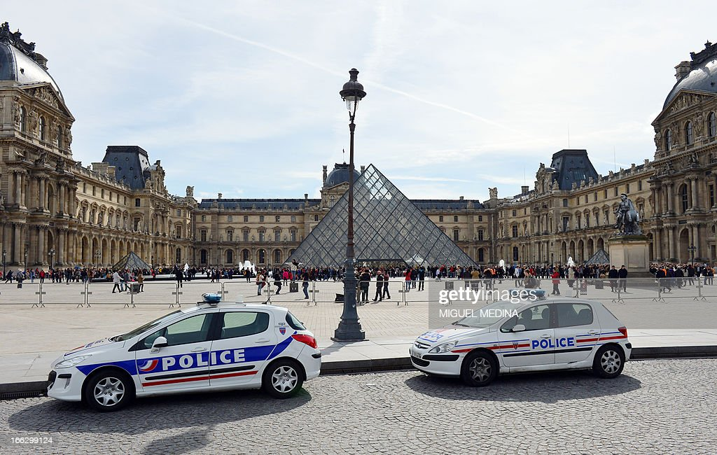 French police cars are parked on April 11, 2013 at the 'Cour Carree' of the Louvre Museum in Paris. Paris's Louvre museum today reopened its doors to the public after a walkout by some staff in protest at gangs of pickpockets operating at the world famous art gallery. Around 20 police officers have now been drafted in to patrol the museum in response to staff concerns, Louvre officials told AFP. The day before, the Louvre failed to open when around 200 employees refused to work saying the museum had become plagued by gangs of increasingly aggressive pickpockets, many of whom were children.