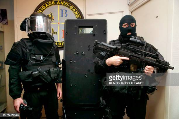 French police commandos of the Search and Intervention Brigade pose with a bullethole riddled riot shield in Paris on November 17 which was used...