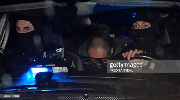 French police escort suspect Hubert Caouissin to the home of Lydie Troadec sister of Pascal Troadec who went missing with his wife and two children...