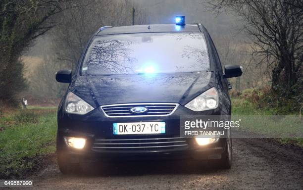 French police escort suspect in the Troadec case Hubert Caouissin out of his home on March 8 2017 in PontdeBuis western of France A crowbar was the...