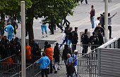 French police forces stand near Stade de France's security staff controling Marseille's supporters arriving at the entrance of the stadium prior to...