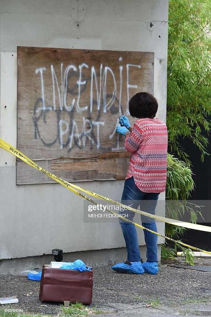 A French police forensic expert takes samples while searching for evidence on June 30, 2016 in Bordeaux, after the headquarters of the local French CFDT trade union were damaged overnight by a intentional garbage fire set in front of the building. / AFP / Mehdi FEDOUACH