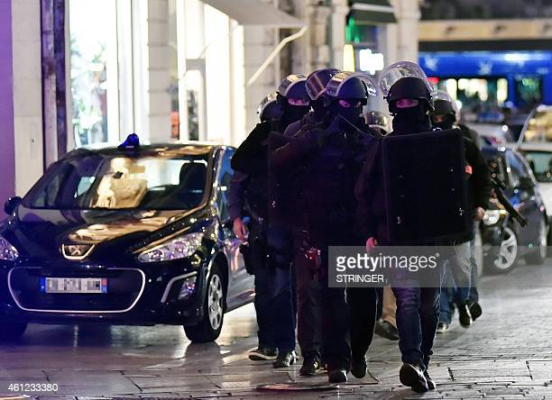 French police in protective gear arrive in the area where two people are being held hostage in a jewellery store by a gunman attempting a robbery on...