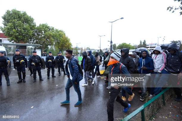 French police look on as migrants walk towards waiting buses as they are evacuated from a makeshift camp at Porte de la Chapelle in the north of...