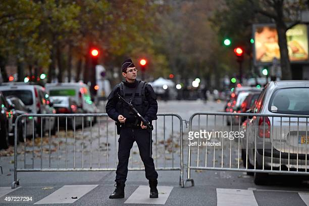 French police man stand guard near the scene of Friday's Bataclan Theatre terrorist attack on November 15 2015 in Paris France As France observes...