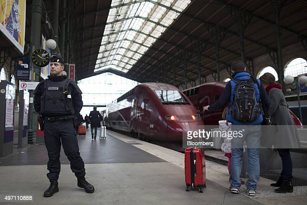 A French police office stands on guard as passengers wait at the Gare du Nord train station in Paris France on Saturday Nov 14 2015 French President...
