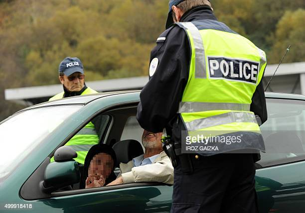 A French police officer checks a person's papers at a border post on the FrenchSpanish border on the A63 motorway in Biriatou southwestern France on...
