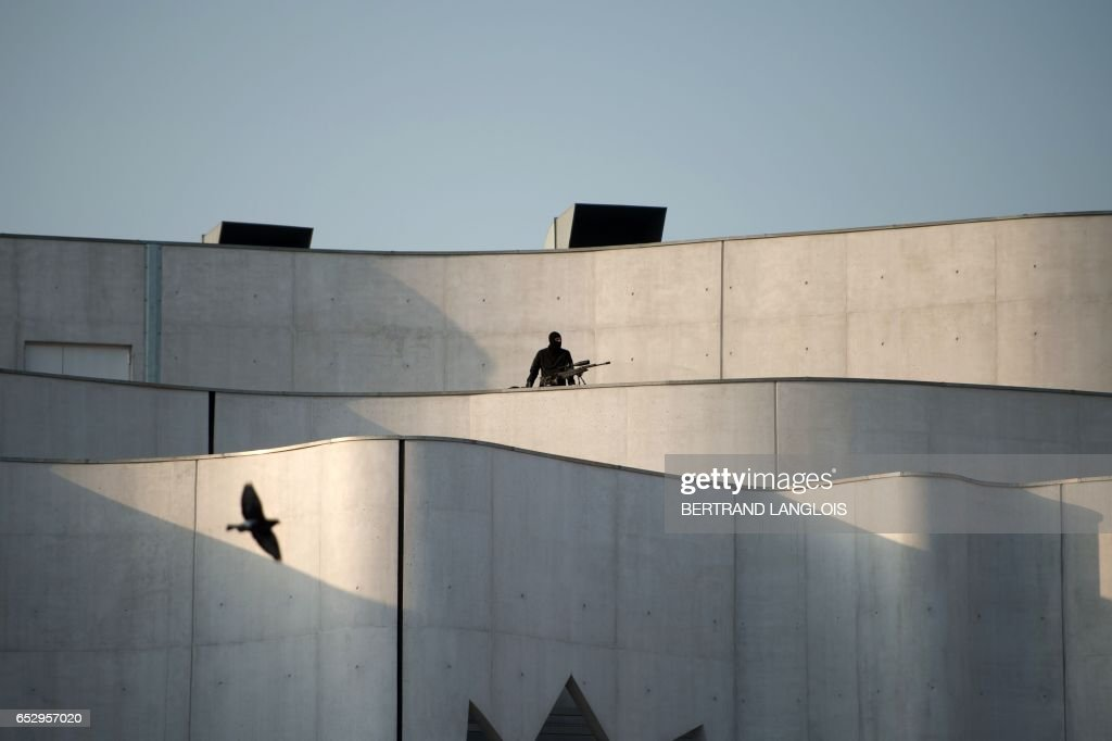 A French police officer is positioned on the roof of the Mediatheque La Passerelle, a multimedia library, during a visit of the prime minister to Vitrolles, southern France, on March 13, 2017. /