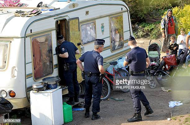 A French police officer looks inside a caravan as French police carry out identity checks at a Roma camp on October 1 2013 in Roubaix northern France...