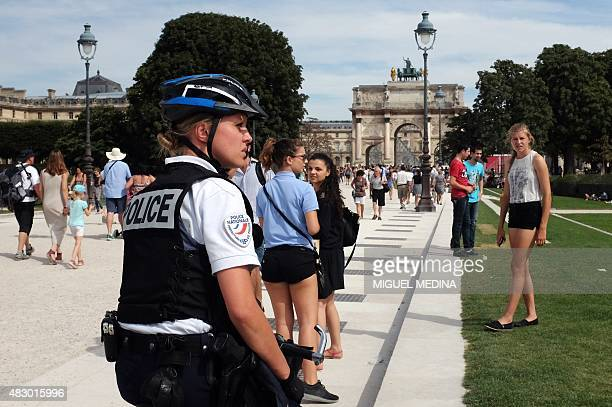 A French police officer patrols in the Tuileries gardens in Paris on August 5 2015 during a crackdown on pickpockets and street scammers targeting...