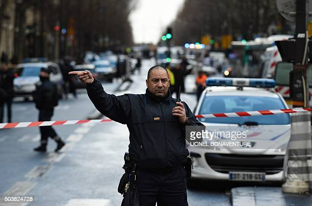 A French police officer redirects traffic at the Boulevard de Barbes in the north of Paris on January 7 after police shot a man dead as he was trying...