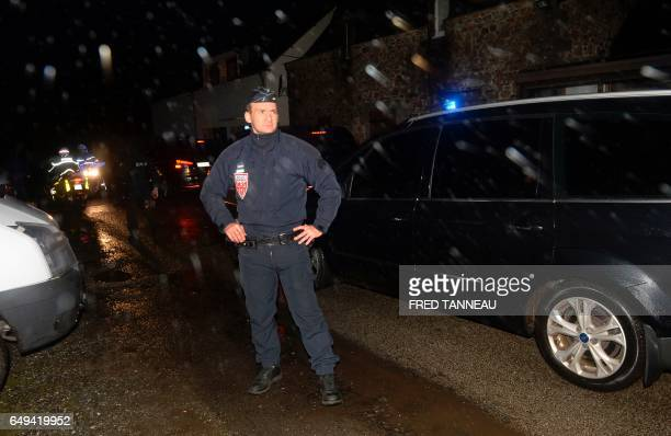 A French police officer stands guard as police escort suspect Hubert Caouissin to the home of Lydie Troadec sister of Pascal Troadec who went missing...