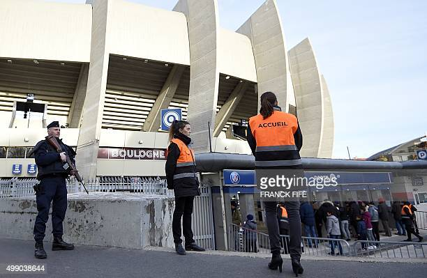 A French police officer stands guard as receptionists wait to greet spectators outside the Parc des Princes stadium in Paris before the French L1...