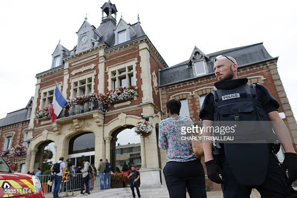 A French police officer stands guard by SaintEtienneduRouvray's city hall following a hostagetaking at a church in SaintEtienneduRouvray northern...