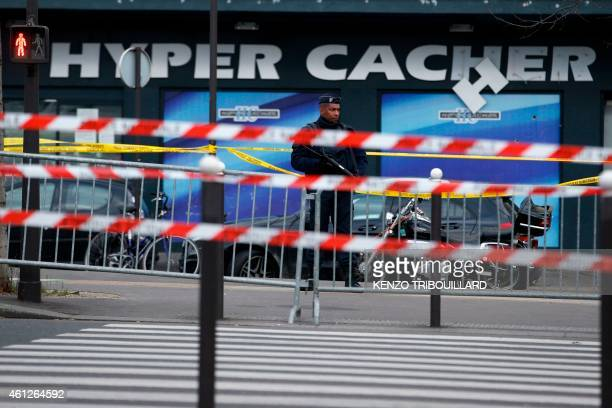 A French police officer stands guard in front of a kosher grocery store in Porte de Vincennes eastern Paris on January 10 2015 a day after four...