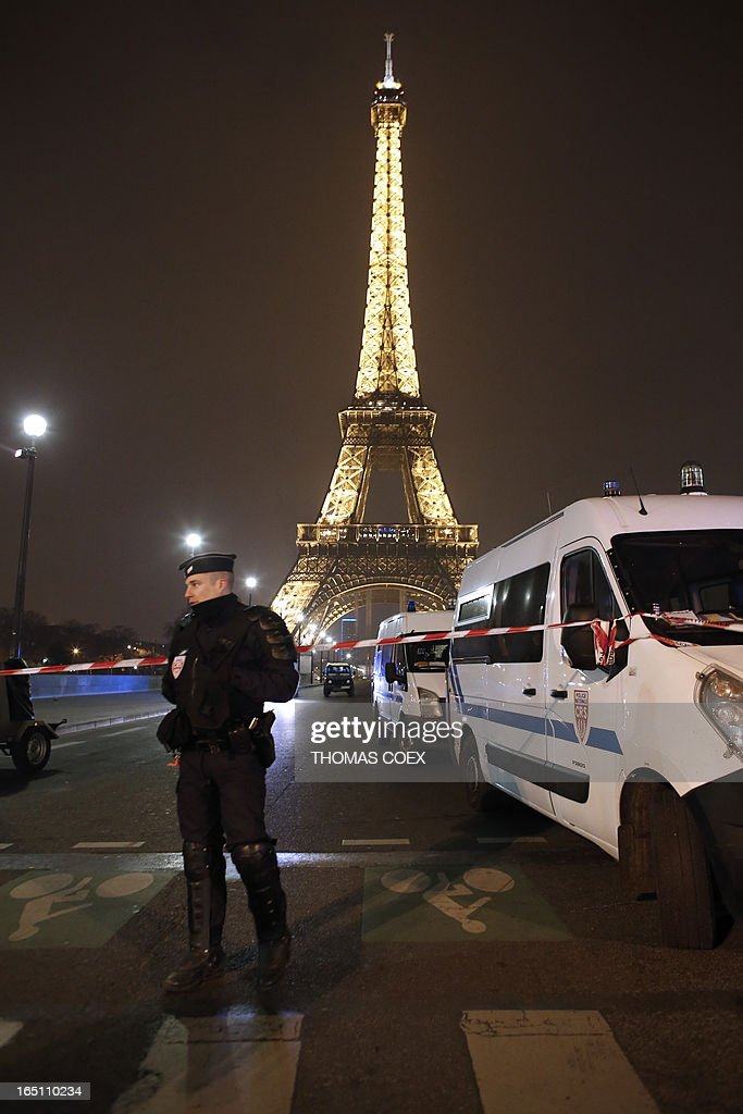 A French police officer stands guard near Eiffel Tower in Paris on March 30, 2013. The Eiffel Tower was evacuated in the evening on March 30 after an anonymous phone call announced an attack, said a police source. The perimeter of the monument was secured and about 1,400 people were evacuated shortly before 21h00.