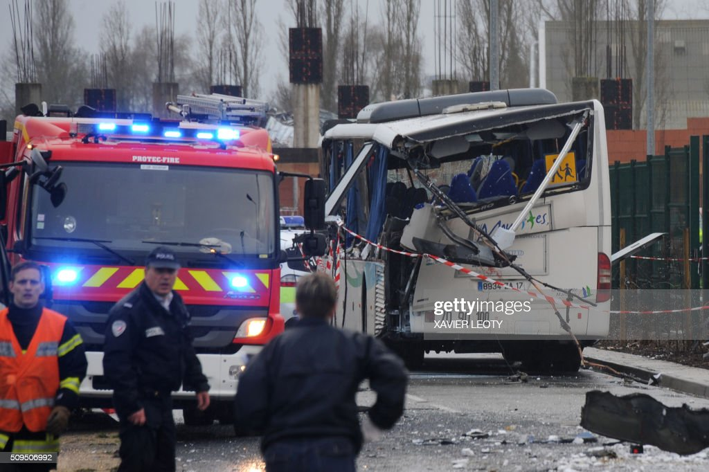 A French police officer stands near the wreckage of a school minibus after it crashed into a truck near Rochefort on February 11, 2016, killing at least six children, police said, a day after another road accident involving a school bus left two youngsters dead. The head-on smash with a lorry carrying rubble came around 7:15 am (0615 GMT) near Rochefort in the western Charente-Maritime region. / AFP / XAVIER LEOTY