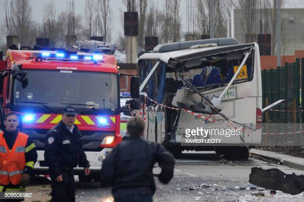 A French police officer stands near the wreckage of a school minibus after it crashed into a truck in Rochefort on February 11 killing at least six...