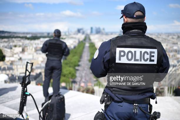 A French police officer stands next to an antidrone gun on top of the Arc de Triomphe during the annual Bastille Day military parade on the...