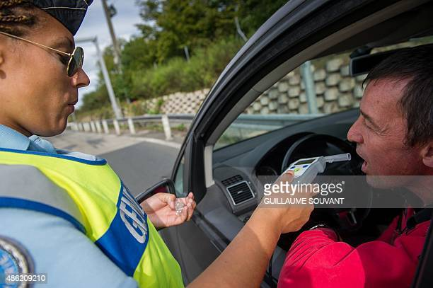 French police officer stops a car for an alcohol control near the tollgate of Monnaie on the highway A10 on august 16 2015 AFP PHOTO / Guillaume...