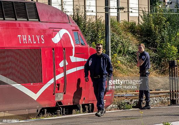 A French police officer walks along the platform next to a Thalys train of French national railway operator SNCF at the main train station in Arras...