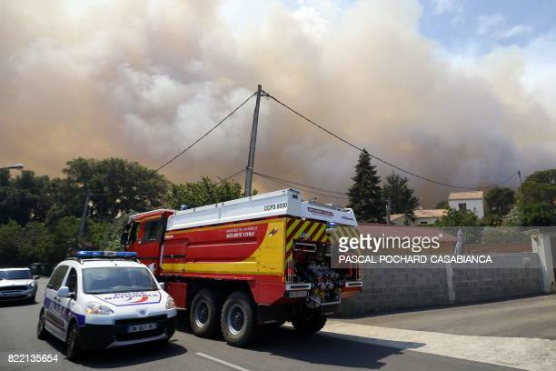French police officers and French firefighters arrive on the site of the blaze to extinguish the fire burning the forest in Ortale de Biguglia near...