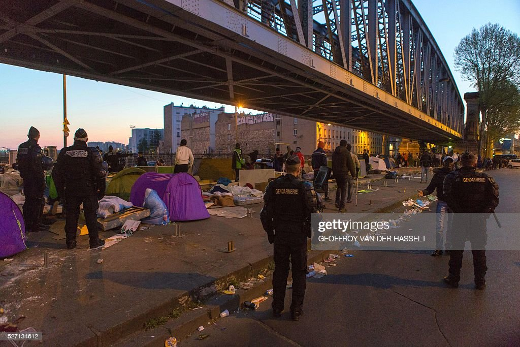 French police officers and gendarmes evacuate migrants from a makeshift camp under the Stalingrad metro station in Paris, on May 2, 2016. / AFP / Geoffroy Van der Hasselt