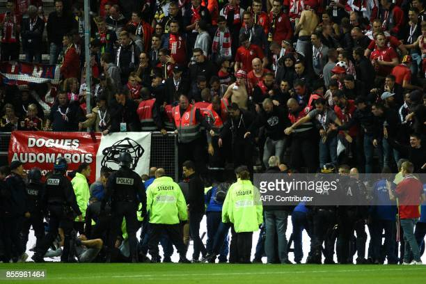 French police officers and members of the stadium staff gather to help LOSC's supporters following the fall of their tribune during the French L1...