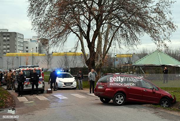 French police officers and soldiers stand near a red car in front of the mosque of Valence southeastern France on January 1 after a soldier guarding...