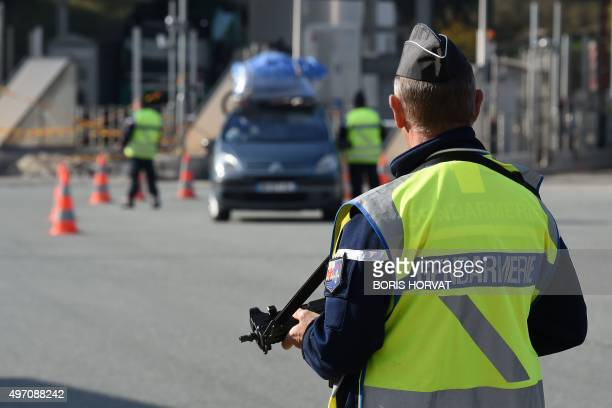 French police officers control a vehicle at the FrenchItalian border on November 14 2015 in Menton European capitals reinforced security checks as...