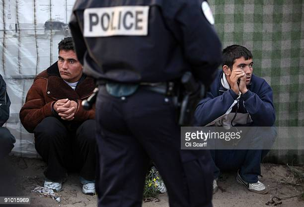 French police officers detain migrants and protesters from the makeshift migrant camp known as 'The Jungle' adjacent to a ferry terminal to the UK on...